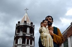 Low-cost, decent Statue Of Joseph With infant Jesus infront of Del Remedio church building tower. San Pablo City, Laguna, Philippines - December 14, 2016: Low Royalty Free Stock Images