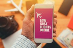 Low cost flights online mobile phone app. Man holding smartphone with mock up application screen related to holiday vacation journey trip royalty free stock image