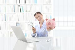 Low cost and saving search concept, smiling woman working at off. Ice desk on computer with magnifying glass and piggy bank royalty free stock photo