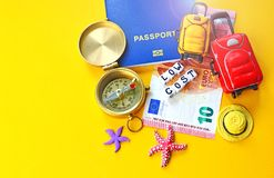 Low cost travel concept background with biometric passport id, euro, compass, miniature baggage and sea accessories. Low cost travel concept background with stock photos