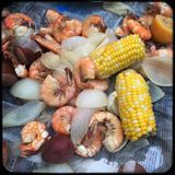 Low country shrimp boil. Low country boil of shrimp in shell with corn on the cob and onions on newspaper Stock Photos
