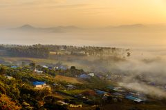 Low crawling fog to a village and scenic of mountain in sunrise royalty free stock photography