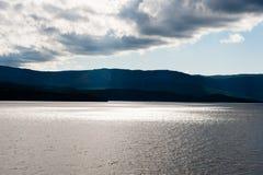 Low dark clouds above illuminated water at steep coast Royalty Free Stock Photos