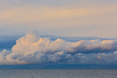 Low dramatic fluffy clouds over sea water Stock Photo