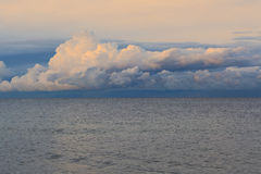 Low dramatic fluffy clouds over sea water Stock Photography