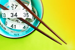 Low-fat asian cuisine. A pair of chopsticks rests on a bowl with a tape measure stock photo