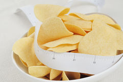 Low fat potato chips. Closeup of a bowl with low fat potato chips and a measuring tape Royalty Free Stock Photos