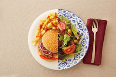 Low fat salad against greasy burger Royalty Free Stock Image