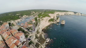 Low flight over old city Bonifacio at golden sunset colors. Corsica, France. Aerial view. stock video footage