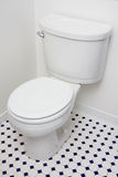 Low flow toilet. In corner of white bathroom with tile floor Stock Image