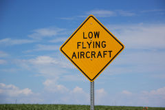 Low flying aircraft sign. Low flying aircraft warning sign against blue skies in field of green on sunny day Royalty Free Stock Photos