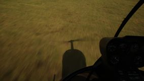 Low-flying helicopter flight over the field, helicopter shadow on the grass. Small lightweight aviation.