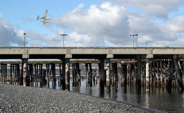 Low flying seaplane and dock Royalty Free Stock Photos