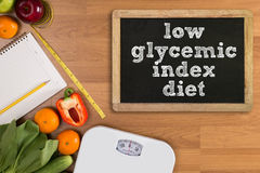 Low glycemic index diet. Fitness and weight loss concept, dumbbells, white scale, fruit and tape measure on a wooden table, top view, free copy space Stock Image