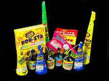 Low Grade hand held fireworks like Pop Its and Party Poppers on a black backdrop Royalty Free Stock Photography