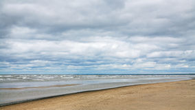 Low gray clouds over beach of Baltic Sea in autumn Stock Photos