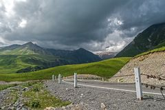 Low gray clouds over mountain road. Serpentine Stock Photo