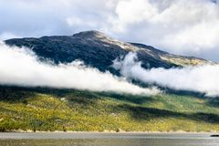 Low hanging clouds over mountainside coastline stock photo