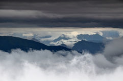 Low hanging clouds swirl around ridges of Carnic Alps, Italy. Low hanging cloud layers swirl around and above the ridges of Carnic Alps and Julian Alps in the Royalty Free Stock Photo