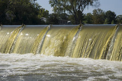 Low Head Dam Spillway. Water spilling over the flashboards of a low head dam on the Fox River, Wisconsin Royalty Free Stock Photo
