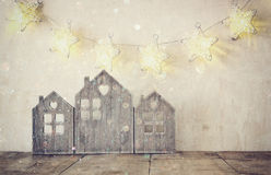 Low key and abstract filtered image of vintage wooden house decor on wooden table and stars garland Royalty Free Stock Image