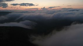 Low key aerial view evening flight over clouds and hills in the mountains at blue hour after sunset. The concept of. Evening party and night flights cloudy stock video footage