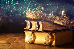 Low key of beautiful queen/king crown on old books. vintage filtered. fantasy medieval period. Low key image of beautiful queen/king crown on old books. vintage stock photography