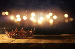 low key of beautiful queen/king crown over wooden table. vintage filtered. fantasy medieval period Royalty Free Stock Images