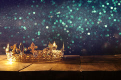 Low key of beautiful queen/king crown over wooden table. vintage filtered. fantasy medieval period. Low key image of beautiful queen/king crown over wooden table Stock Photos