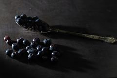 Low key blueberries on a vintage spoon. Low key blueberries on a vintage spoon and dark grey background. Stylish contemporary fresh image of healthy superfood stock photo