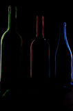 Low-key bottles. Three colored bottles in front of a black background Stock Photos
