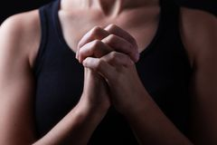 Low key, close up of hands of a faithful woman praying stock photography