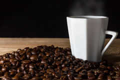 Low key coffee in the darkness. Roasted coffee beans on a wooden table with a glass of white ceramic stock photos