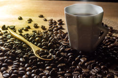 Low key coffee in the darkness. Roasted coffee beans on a wooden table with a glass of white ceramic and a wooden spoon in morning light stock photos