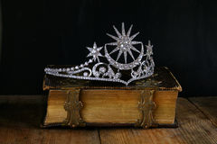 Low key image of beautiful diamond queen crown. On old book. selective focus. medieval period concept Stock Photography