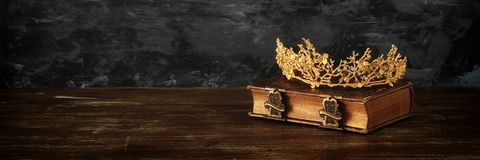 Low key image of beautiful queen crown on old book. fantasy medieval period. Low key image of beautiful queen crown on old book. fantasy medieval period royalty free stock photography