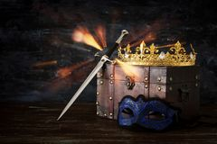 Low key image of beautiful queen/king crown, mysterious mask and sword. fantasy medieval period. Low key image of beautiful queen/king crown, mysterious mask stock photo