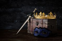 Low key image of beautiful queen/king crown, mysterious mask and sword. fantasy medieval period. Low key image of beautiful queen/king crown, mysterious mask royalty free stock image