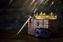 Low key image of beautiful queen/king crown, mysterious mask and sword. fantasy medieval period. Low key image of beautiful queen/king crown, mysterious mask stock image
