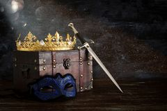 Low key image of beautiful queen/king crown, mysterious mask and sword. fantasy medieval period. Low key image of beautiful queen/king crown, mysterious mask royalty free stock photos
