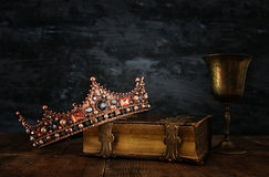 Low key image of beautiful queen/king crown on old book. Next to ancient cup of wine. vintage filtered. fantasy medieval period royalty free stock images