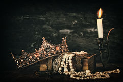 Low key image of beautiful queen/king crown on old book. Next to burning candle. vintage filtered. fantasy medieval period stock image