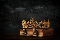 Low key image of beautiful queen/king crown on old book. vintage filtered. fantasy medieval period. Low key image of beautiful queen/king crown on old book royalty free stock photos