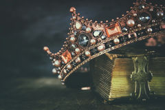 Low key image of beautiful queen/king crown on old book. Vintage filtered. fantasy medieval period royalty free stock image