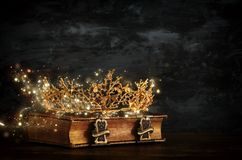 low key image of beautiful queen/king crown on old book. vintage filtered. fantasy medieval period. stock photo