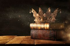 Low key image of beautiful queen/king crown on old books. fantasy medieval period. Selective focus. Low key image of beautiful queen/king crown on old books stock photos