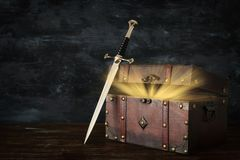 low key image of beautiful queen/king crown, open chest with treasure and sword. fantasy medieval period. royalty free stock image