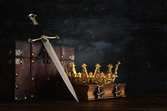 Low key image of beautiful queen/king crown over antique book, chest and sword. fantasy medieval period. Low key image of beautiful queen/king crown over stock images