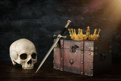 Low key image of beautiful queen/king crown over old chest , human skull and sword. fantasy medieval period. Low key image of beautiful queen/king crown over royalty free stock photos