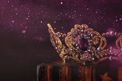 Low key image of beautiful queen/king crown over wooden table. vintage filtered. fantasy medieval period. Low key image of beautiful queen/king crown over royalty free stock image